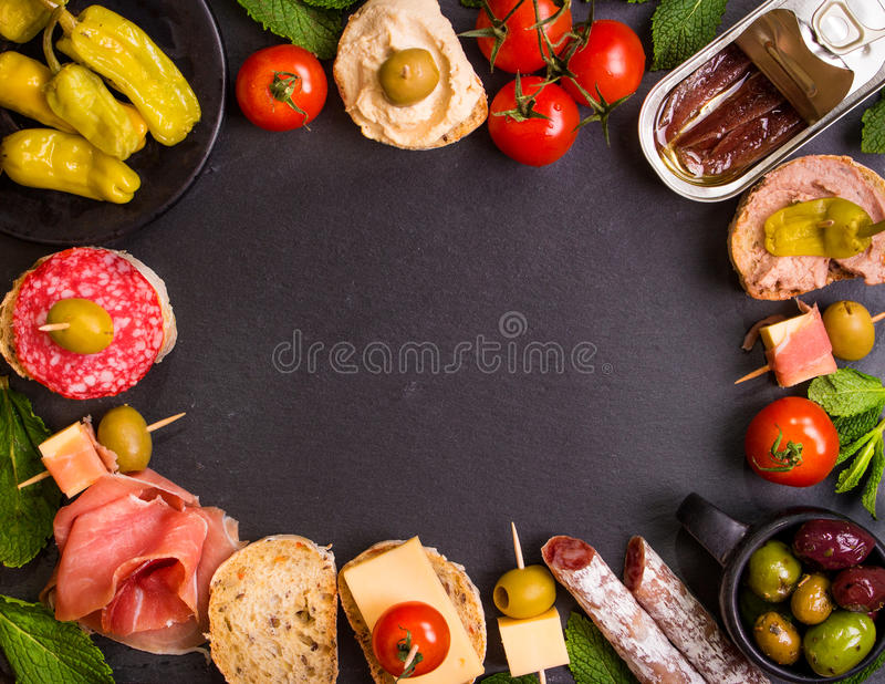 Spanish tapas on a black stone background. Mix of different snacks and appetizers. Spanish tapas on a black stone background. Tapas bar. Space for text. Deli stock image