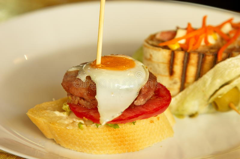 Spanish tapas with quail egg on top. Picture of a small spanish tapas, made from a small burger and having on top a quail fried egg royalty free stock photography