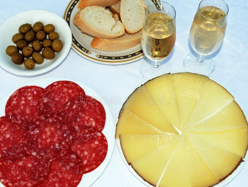 Spanish tapas and sherry. A selection of Spanish tapas including Manchego cheese, green olives and salami with two glasses of fino sherry, Andalusia, Spain royalty free stock photo