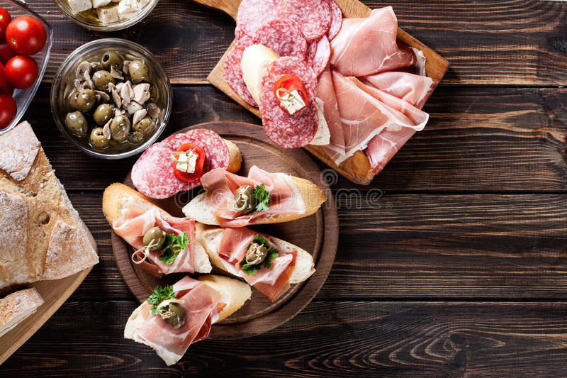Spanish tapas with slices jamon serrano, salami, olives and chee. Se cubes on a wooden table. Spanish cuisine. Top view royalty free stock image