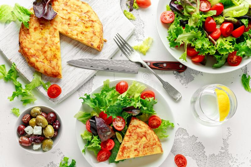 Spanish tortilla, omelette with potato, onion, vegetables, tomatoes, olives and herbs in a white plate. breakfast royalty free stock photos