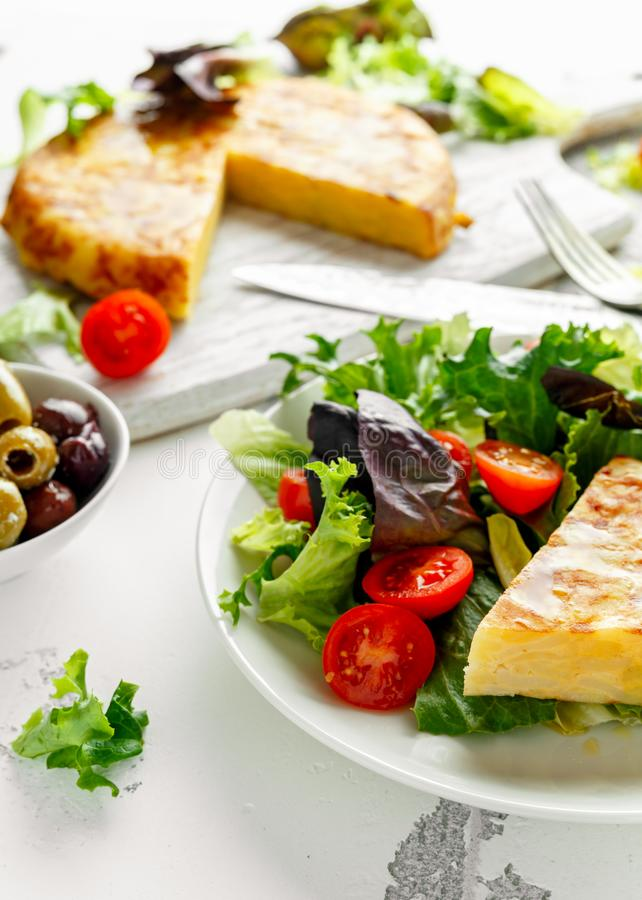 Spanish tortilla, omelette with potato, onion, vegetables, tomatoes, olives and herbs in a white plate. breakfast stock image