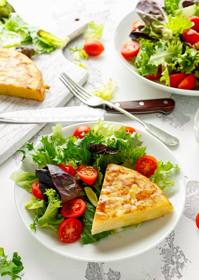Spanish tortilla, omelette with potato, onion, vegetables, tomatoes, olives and herbs in a white plate. breakfast stock photography