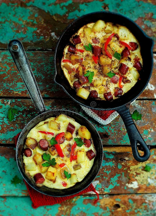 The Spanish tortilla with potatoes and sausages in small frying pans. top view. stock photo