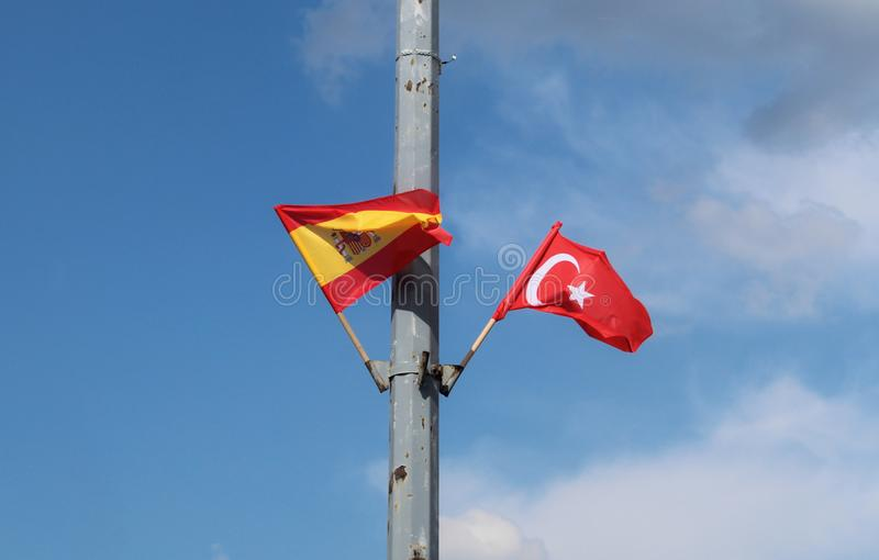 Spanish and Turkish flags in the flagpole on the street lantern with the blue sky in the background.  royalty free stock photos