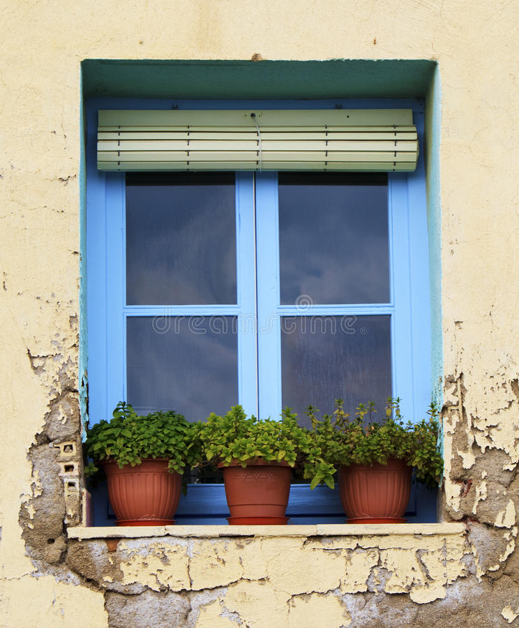 Spanish window. A blue window in an aged Spanish house with plant pots on the window ledge sill stock photos