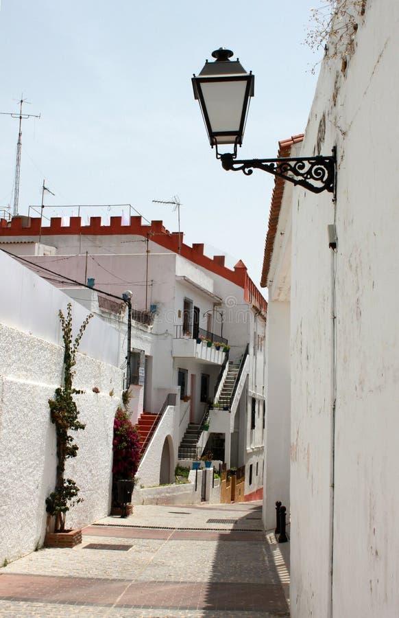 spanje Andalucia Mijas Straat met witte muren van huis, bloemen en straatlantaarn, verticale mening stock foto