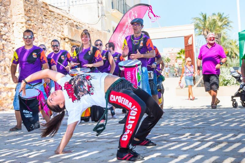 Spanje-TORREVIEJA, ALICANTE - 16 die JUNI, van oung Vrolijke Mensen van 2018 de Trommelpercussie Vrouwenmeisje slaan toont Capoei stock afbeeldingen
