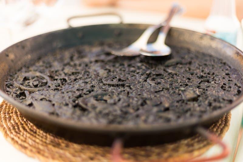 Spanjoren svärtar paella som tjänas som på den traditionella pannan arkivbild