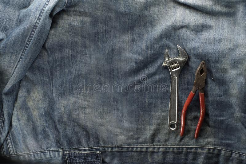Spanner, adjustable wrench, wire cutters, pliers, isolated on labor jacket. Labor day concept. Joinery tools on labor day concept. Spanner, adjustable wrench stock image