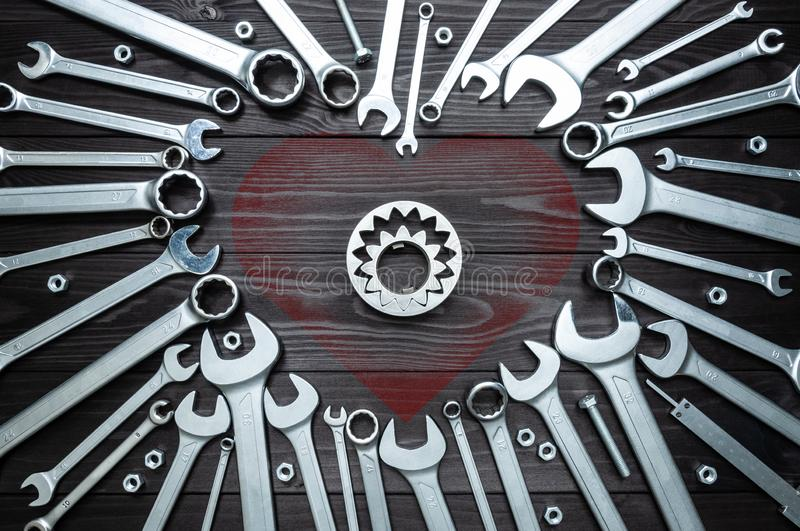 Spanners gears and heart on dark wooden background. concept of love for their work. Spanners gears and heart on a dark wooden background. The concept of love for royalty free stock images