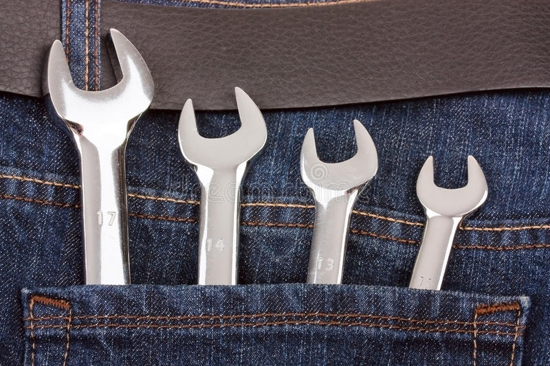 Spanners in jeans pocket. Close up royalty free stock photography