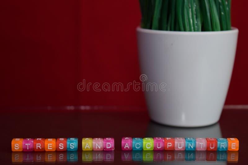 Spanning en accupunturetekst bij kleurrijk houten blok op rode achtergrond Bureaubureau en onderwijsconcept royalty-vrije stock foto