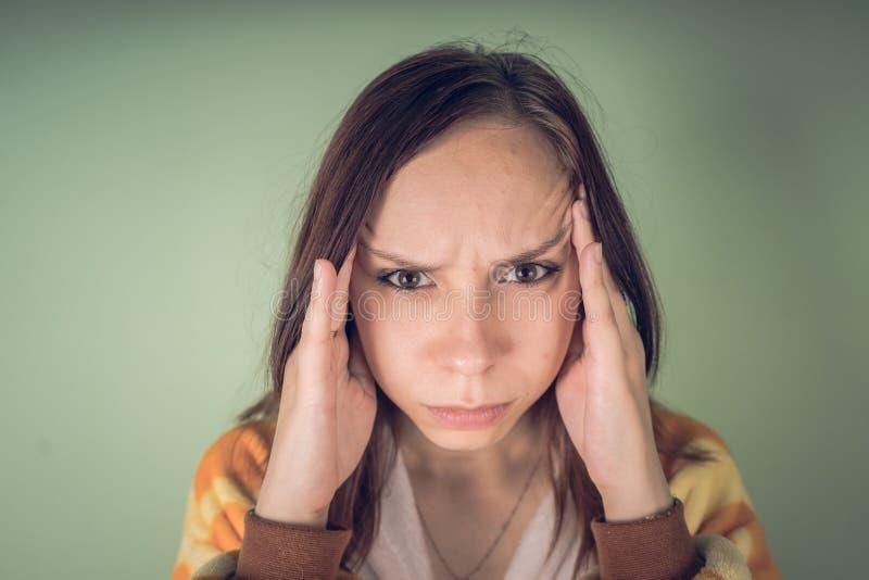 Spanning en hoofdpijn - tienermeisje die migrainepijn hebben Leuk kind die aan een hoofdpijn lijden Ongelukkige Kaukasische tiene stock afbeelding