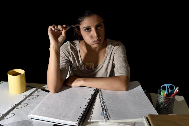 Spansk flicka som studerar den tröttade och borrade hemma sent - natten som ser ledsen och stressad förberedande examen royaltyfri bild