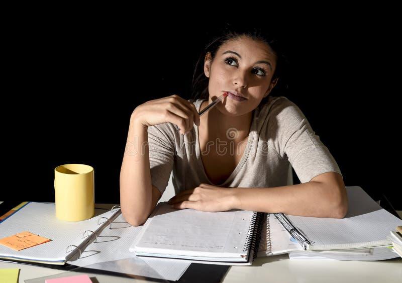 Spansk flicka som studerar tröttat och borrat hemma sent - frånvarande sinnat se för natt fundersamt och lyckligt royaltyfria bilder