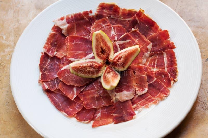 Spansk kokkonsttapasmat Jamon med fikonträdet Härliga aptitskivor av rått grisköttkött, vit plattabakgrund royaltyfri bild