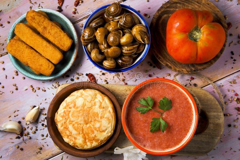 Spansk omelett, gazpacho, sniglar, fiskpinnar royaltyfri foto