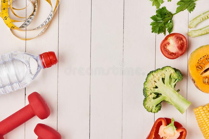 Spansk peppar med att mäta bandet, hantlar och flaskan av vatten, arkivbild