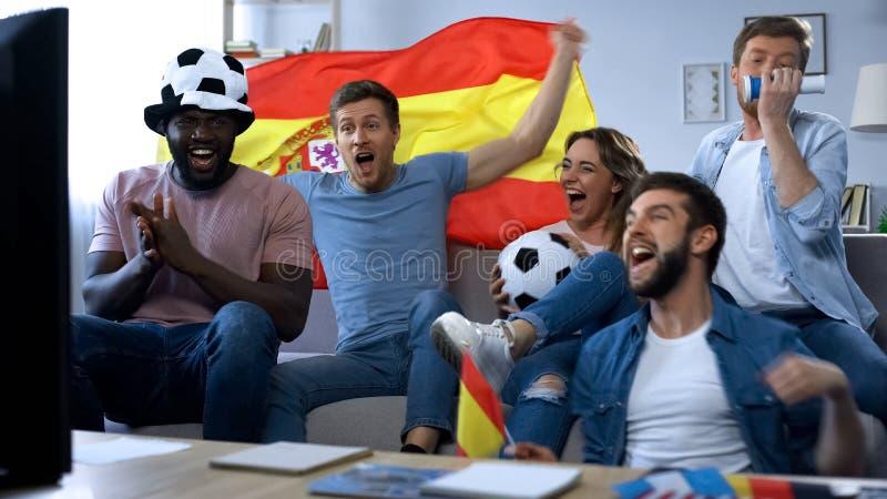 Spanska fans som hemma firar målet, hållande ögonen på match på tv, samhörighetskänsla royaltyfri fotografi