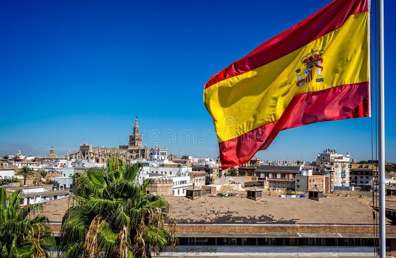 Spanskt flaggaflyg med den Seville domkyrkan i bakgrunden i Seville, Spanien royaltyfria foton