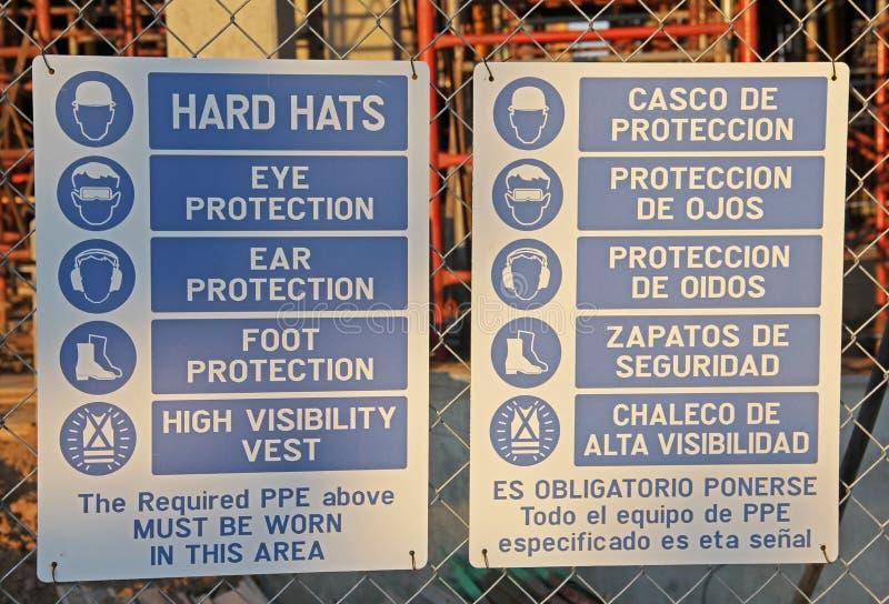 Spanskt tecken för hård hatt för konstruktion som är på engelska och arkivfoto
