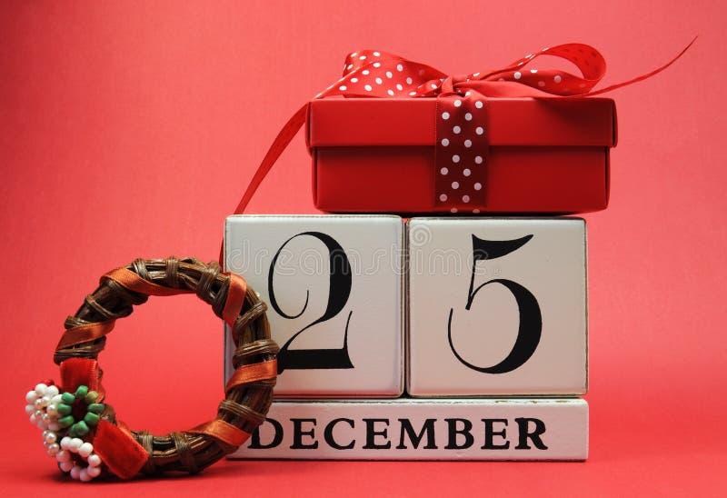 Spara datumet för juldag med denna vita träkvarterkalender för December 25, med en festlig röd närvarande gåva royaltyfri fotografi