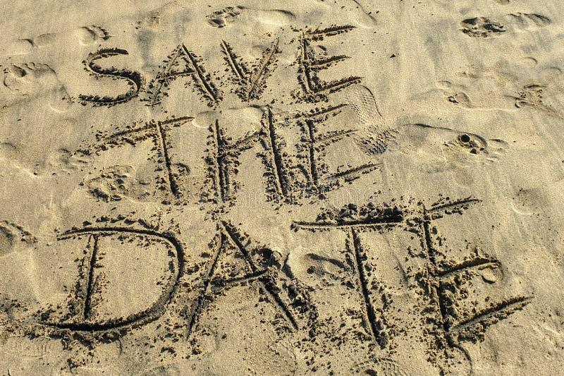 Spara det skriftliga datumbegreppet på sandstranden royaltyfria bilder