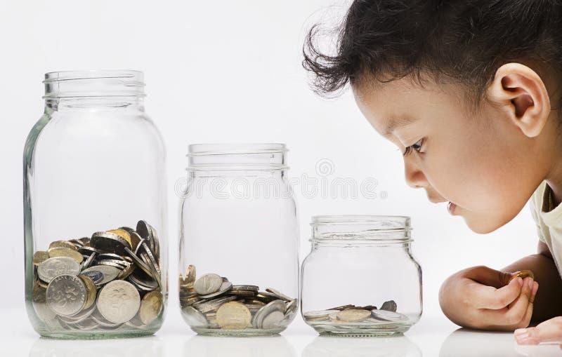 Sparande Begrepp-barn liten flicka som ser mynt i flaskan arkivbild