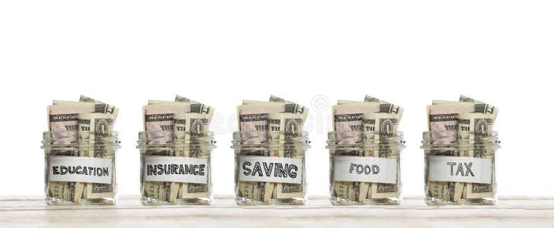 Sparande exponeringsglaskrus med oss dollarpengar för utbildning, försäkring, mat och skatt på träbräde mot vit bakgrund royaltyfri bild