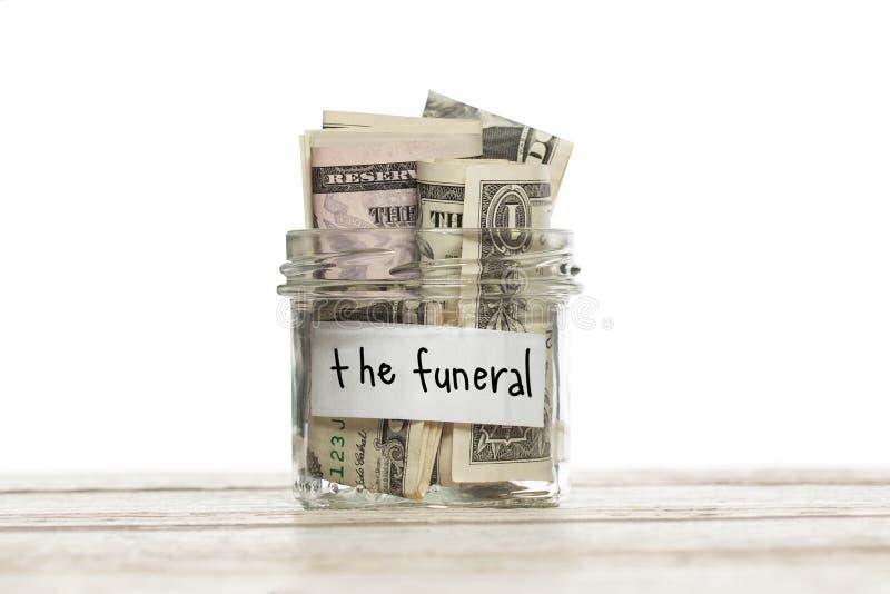 Sparande krus med pengar för begravningen på den isolerade vita trätabellen arkivbilder