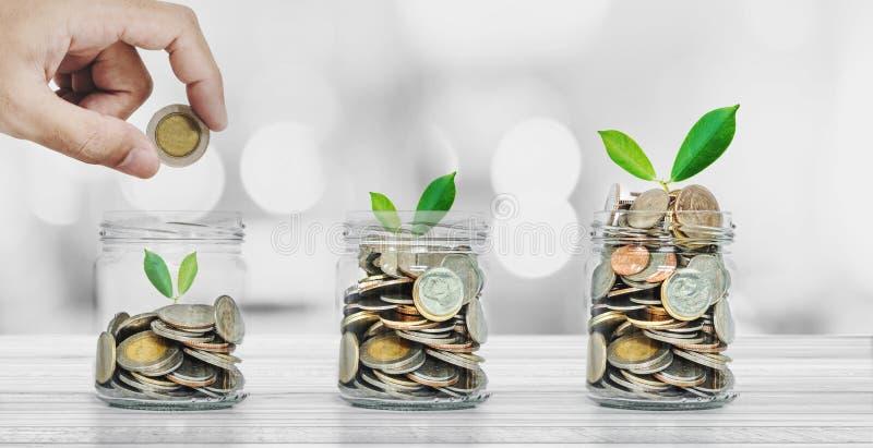 Sparande pengar, bankrörelse- och investeringbegrepp, hand som sätter myntet i glasflaskor med att glöda för växter arkivbild