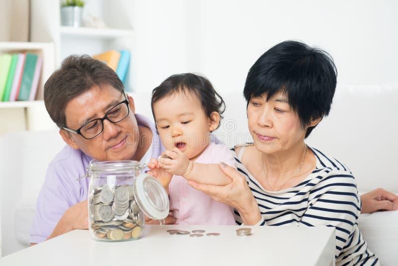Sparande pengar för asiatisk familj inomhus royaltyfria foton