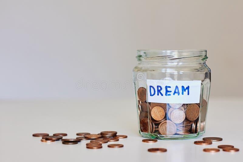 Sparande pengar för dröm- begrepp Glass krus mycket av mynt och teckendrömmen royaltyfri foto