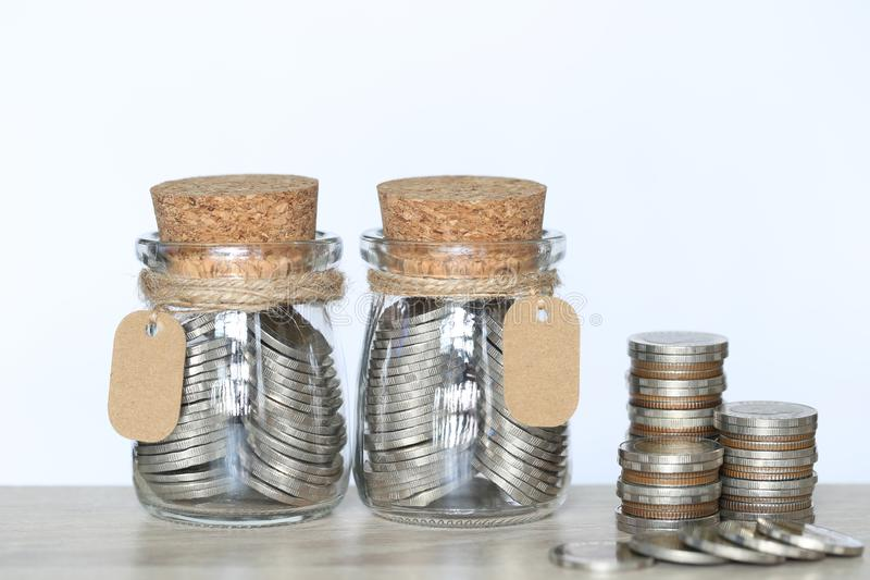 Sparande pengar för förbereder sig i det framtida begreppet, bunt av myntpengar och glasflaskan på wtitebakgrund arkivbilder