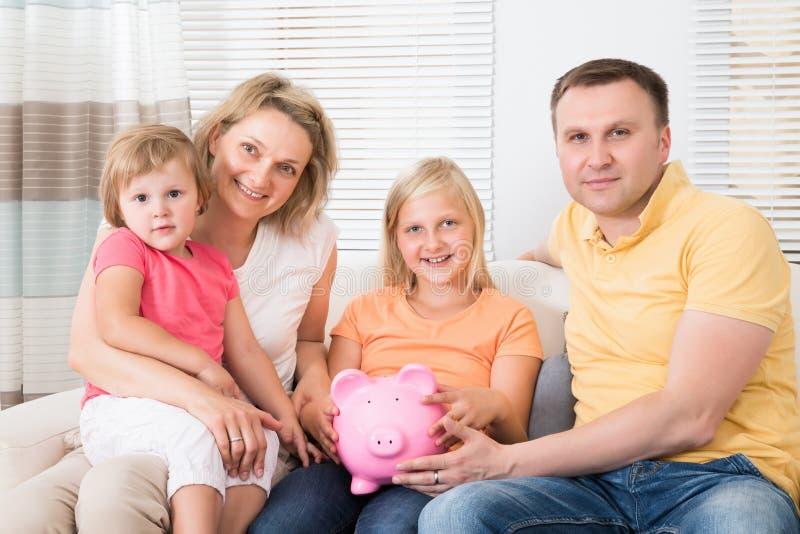 Sparande pengar för familj i piggybank royaltyfri bild