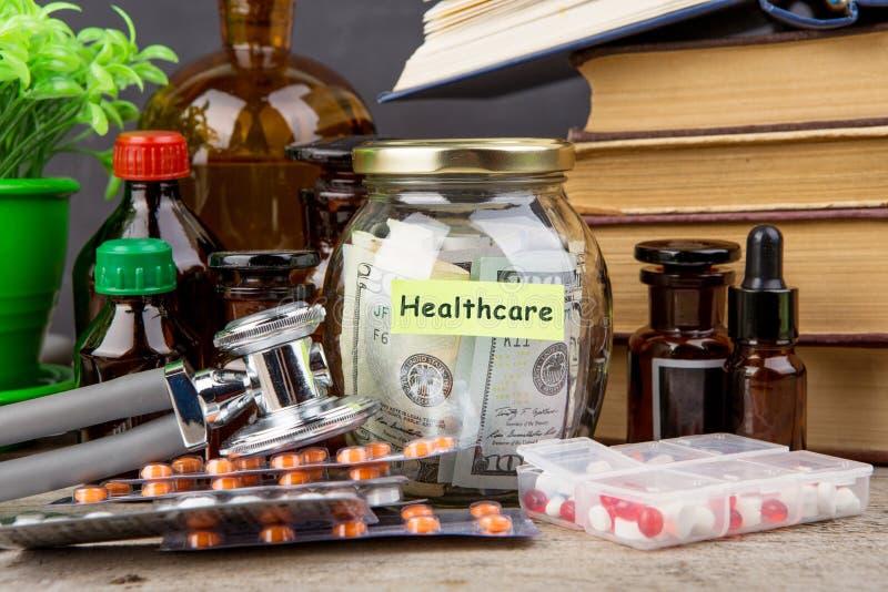Sparande pengar för hälsovårdförsäkring - pengarexponeringsglas, stetoskop, preventivpillerar och flaskor royaltyfria bilder