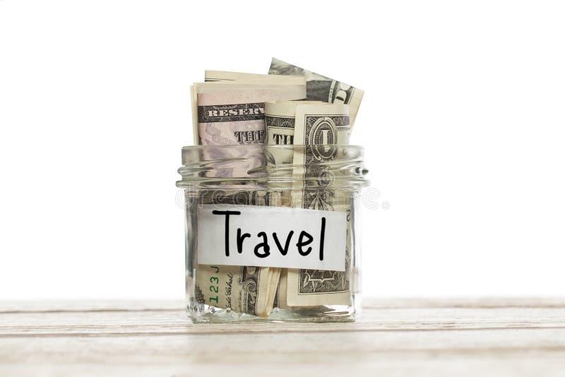 Sparande pengar för loppbegrepp Exponeringsglaskrus med oss dollar för semester på den isolerade trätabellen royaltyfria foton