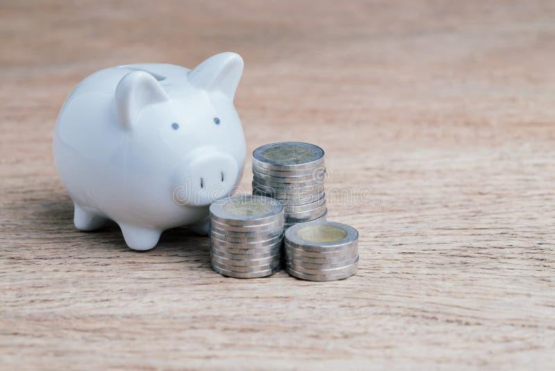 Sparande pengar, finans, budget och skuld med den vita staplade spargrisen och mynt på trätabellen royaltyfria foton