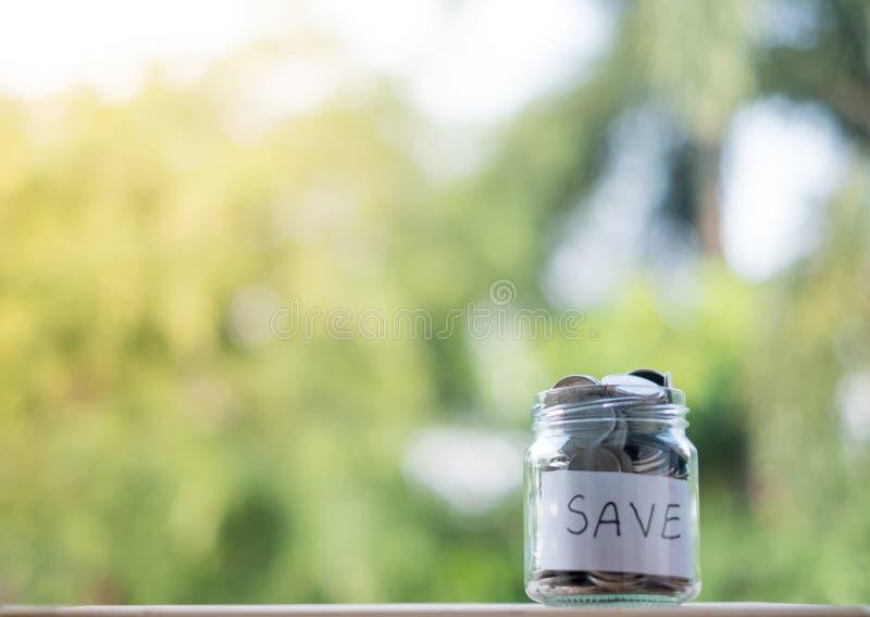 Sparande pengar in i flaskan för den framtida investeringen för kassa in, med en grön bakgrund fotografering för bildbyråer
