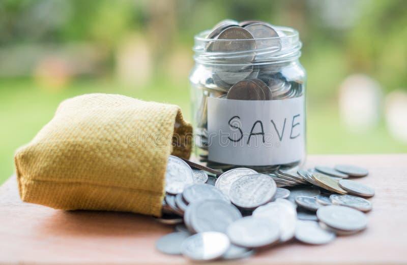 Sparande pengar in i flaskan för den framtida investeringen för kassa in, med en grön bakgrund royaltyfri foto