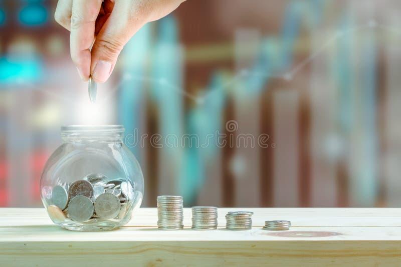 Sparande pengar- och investeringbegrepp, hand som sätter myntet i glasflaskan för att besparingar och buntmynt ska visa förhöjnin royaltyfri fotografi