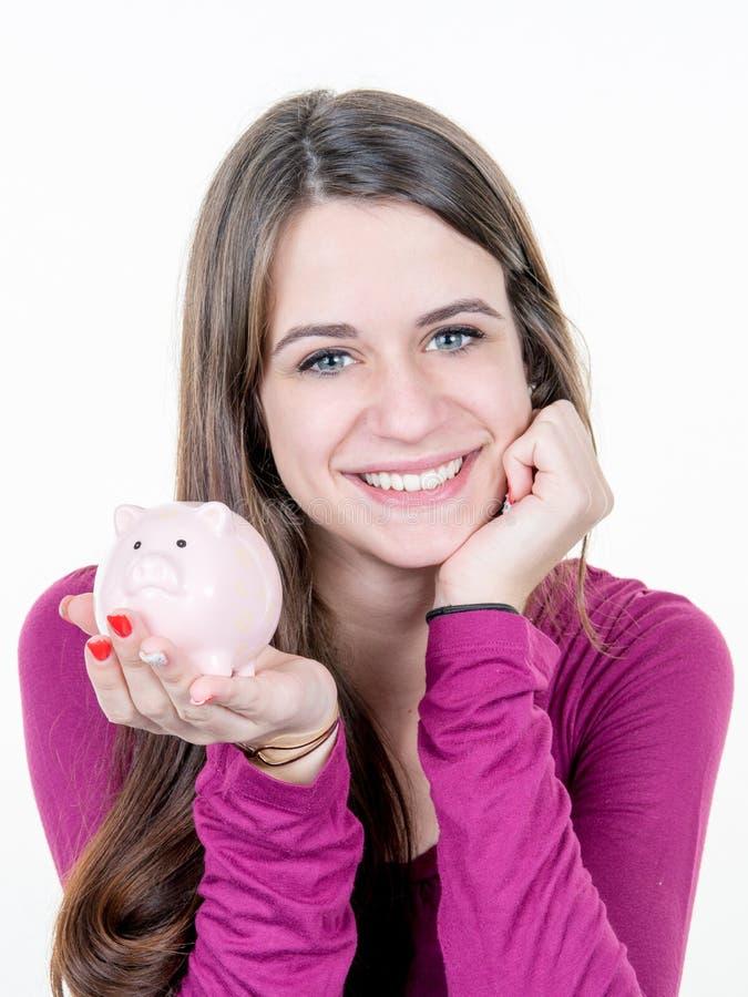 sparar den nätta flickan för kvinnan med en rosa spargris på vit bakgrund för pengarbegrepp fotografering för bildbyråer