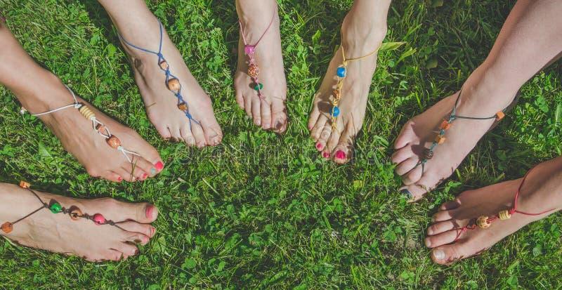 Sparate con i piedi delle donne nell'erba, le perline ornate, la meditazione, il allenamento, la costruzione di squadre Persone,  immagine stock