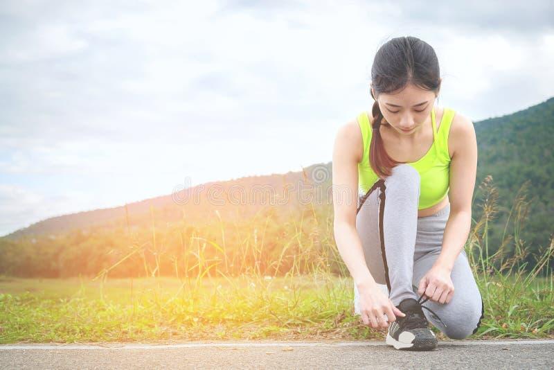 Sparato del corridore della giovane donna che stringe i pizzi di scarpa da corsa, ottenendo immagine stock