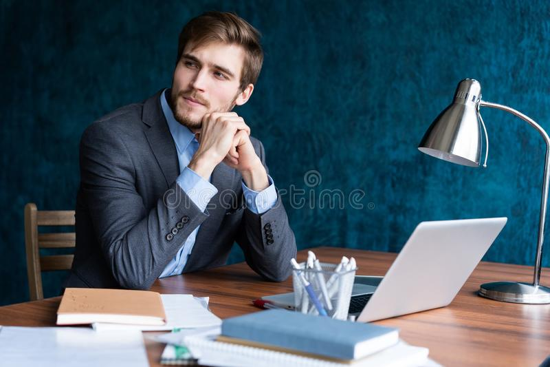 Sparato del giovane che si siede alla tavola che distoglie lo sguardo e che pensa Uomo d'affari premuroso che si siede nell'uffic immagine stock