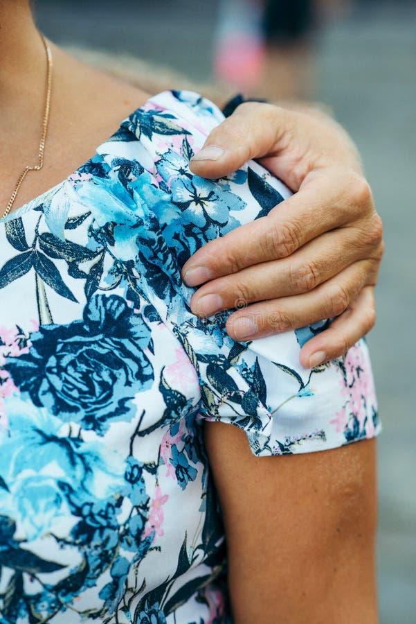 Sparato della parte del corpo della donna nella camicia colourful La mano maschio sta abbracciando tenero la sua spalla Nessun fr fotografie stock