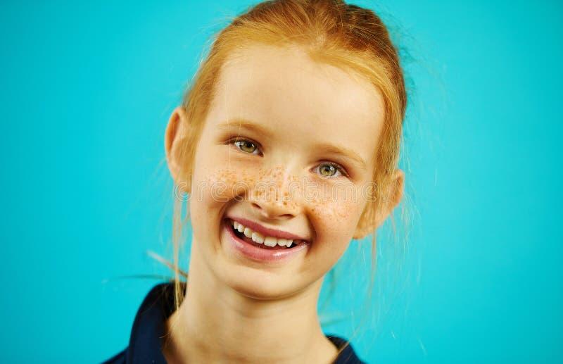 Sparato della ragazza redheaded sveglia nell'umore allegro, sorridere francamente, godente dell'evento sul blu ha isolato il fond fotografia stock