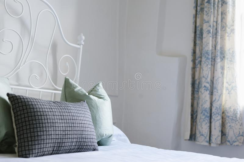 Sparato di un letto bianco con i cuscini blu e blu-chiaro immagine stock