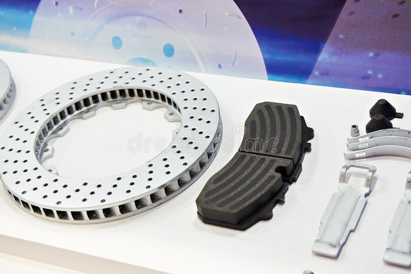 Spare parts brake disc and brake pad for car in store. Spare parts for the car. Brake disc and brake pad royalty free stock photos
